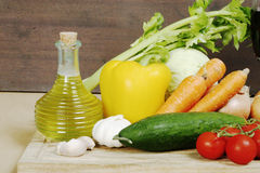 Various vegetables and olive oil on desk Stock Images