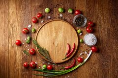 Various vegetables, seasoning and spicies around blank plate on rustic wooden background, top view royalty free stock photo