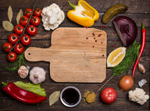Various vegetables and spices and empty old cutting board. Color Stock Photos