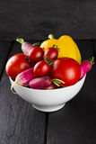 Various vegetables: tomatoes, cherry tomatoes, radish, pepper in. White bowl on brown wooden background Royalty Free Stock Image