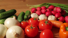 Various vegetables on wooden table. A variety of bright vegetables spread over a wooden table stock footage