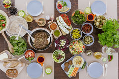 Various vegetarian dishes on table. Various colorful vegetarian dishes lying on wooden table Royalty Free Stock Photo