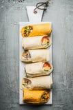 Various vegetarian tortilla wraps on white cutting board Royalty Free Stock Image