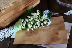 Bouquet of fresh lilies of the valley and retro book Stock Photo