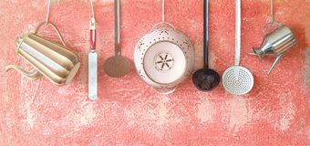 Various vintage kitchen utensils on a rustic wall Stock Images