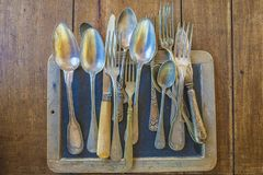 Various vintage knives, spoons, forks on old blackboard Royalty Free Stock Photos