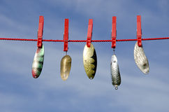 Various vintage metal lures - spoons on cloth string and sky Stock Image