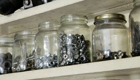 Various vintage old jars with metal bolts, nuts and screws on wooden cupboard in workshop. Closeup photo on containers in workshop Royalty Free Stock Photo