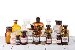 Various vintage pharmacy bottles on wooden table in pharmacy Stock Photos