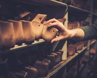 Various of vintage wooden shoe lasts in a row on the shelves. Stock Photos