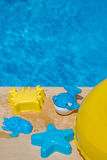 Various water toys on the side of a swimming pool. Yellow and blue pool float and toys placed on the side of the swimming pool, pool ring in cool blue refreshing Royalty Free Stock Photo