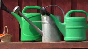 Various watering cans on table near farm barn wooden wall. Various watering cans on table near farm barn red wooden wall stock video