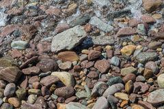 Various wet stones. By the water edge Stock Photos