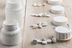 Various white plastic pill bottles and heap of drugs. On bright wooden table royalty free stock photo