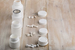 Various white plastic pill bottles and heap of drugs. On bright wooden table stock photo