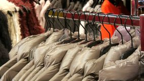 Various women`s winter jackets clothing hanging on hangers in a clothing store in mall or shopping center. Various women`s winter jackets clothing hanging on stock footage
