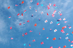 Various world flags against blue sky background. Various world flags on strings flapping in the wind on a blue sky background Royalty Free Stock Photography