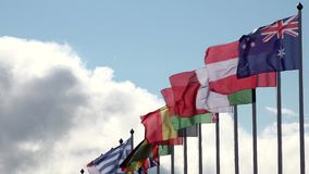 Various world flags flying on flagpoles on a background of the sky and clouds stock video