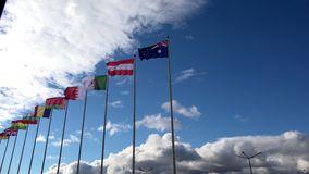 Various world flags flying on flagpoles on a background of the sky and clouds. Various world flags flying on flagpoles stock footage