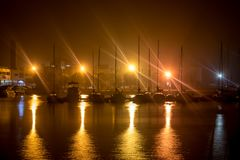 Various yachts at night with lights with star rays stock photos