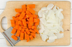 Variously sliced for cooking carrots and onions on a cutting boa Royalty Free Stock Photography