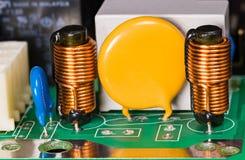 Varistor, induktionsapparater, kondensator och relä på grönt strömkretsbräde royaltyfri foto