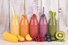 Variété de smoothies de fruit dans des couleurs d'arc-en-ciel avec frais Photographie stock libre de droits