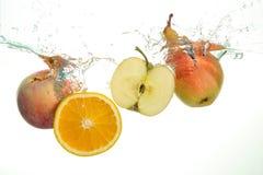 Apple slice, pear and orange splash in water in white stock image