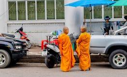 Varje morgon talar två lilla munkar tillsammans, medan gå omkring i den Pranburi staden, Thailand Juni 10, 2017 royaltyfria foton