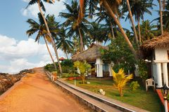 Big bungalow street in the tropical resort. Varkala, India - February 09, 2016: big luxury bungalow street in the tropical resort, palm tree alley, idylic place Stock Images