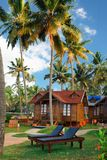 Big wooden bungalow street in the tropical resort. Varkala, India - February 09, 2016: big luxury wooden bungalow street in the tropical resort, palm tree alley Stock Photo