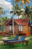 Big wooden bungalow street in the tropical resort. Varkala, India - February 09, 2016: big luxury wooden bungalow street in the tropical resort, palm tree alley Royalty Free Stock Photos