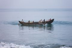 fishermen sail and sighting fish in traditional wooden canoe boat on blue indian ocean Stock Images