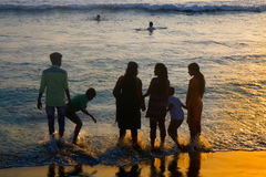 VARKALA, KERALA, INDIA - DECEMBER 15, 2012:. VARKALA, INDIA - Jan 2, 2016: Indians with their families on beach at sunset, swimming Royalty Free Stock Photo