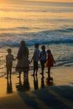 VARKALA, KERALA, INDIA - DECEMBER 15, 2012:. VARKALA, INDIA - Jan 2, 2016: Indians with their families on beach at sunset, swimming Stock Photography