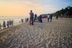 VARKALA, KERALA, INDIA - DECEMBER 15, 2012:. VARKALA, INDIA - Jan 2, 2016: Indians with their families on beach at sunset, swimming Stock Photography