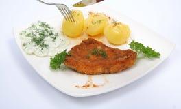 Varkenskotelet en fijngestampte aardappels die worden gesneden Stock Afbeeldingen