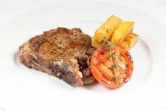 Varkenskoteletlapje vlees met gebraden aardappels en tomaat Hoofdgerechtmenu royalty-vrije stock afbeelding