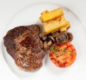 Varkenskoteletlapje vlees met gebraden aardappels, paddestoelen en tomaat stock foto's