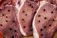 Varkenskoteletten en kruiden op een houten raad Stock Afbeeldingen