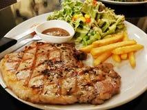 Varkenskoteletten met Frieten en salade Stock Afbeelding