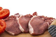 Varkenskoteletten, tomaat en een vleeshamer Royalty-vrije Stock Fotografie