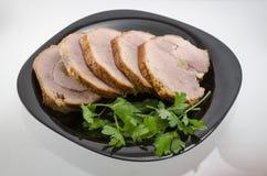 Varkensvlees met knoflook en kruiden op een plaat Stock Foto's
