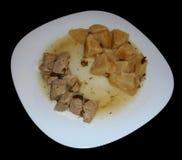 Varkensvlees met knolselder en aardappels op zwarte worden geïsoleerd die Royalty-vrije Stock Foto