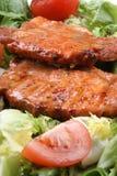 varkensvlees op een bed van sla met tomaten stock afbeelding
