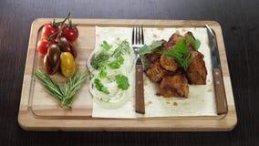 Varkensvlees shashlik met groenten op een houten raad met keukentoestellen stock videobeelden