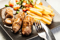 Varkensvleesbroodjes met frieten met groente Stock Foto