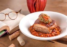Varkensvleesbuik met boonhutspot en fijngestampte groenten stock afbeeldingen