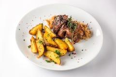 Varkensvleesgewricht met aardappels en kool op een witte plaat Selectieve nadruk Royalty-vrije Stock Foto's