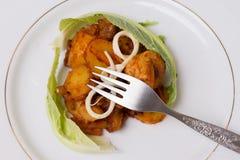 Varkensvleeshutspot met aardappels met kaas en bloemkoolbladeren worden verfraaid dat Royalty-vrije Stock Afbeeldingen